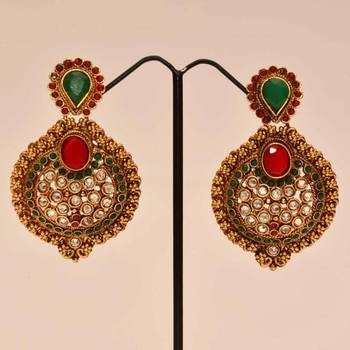 Anvi's classic nawabi earrings studded with white stones, rubies and emeralds