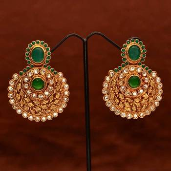 Anvi's designer leaf work ear danglers studded with white stones and emeralds